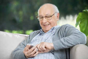 Elderly man smiling and typing on his smartphone