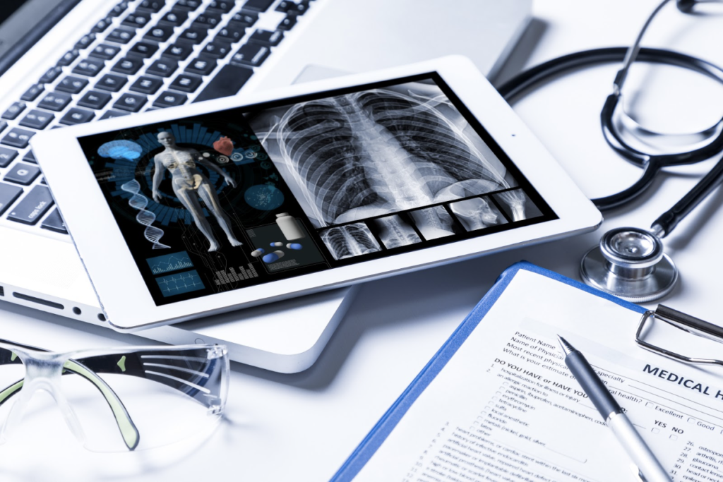 Tablet showing XRays and other medical info, on top of a computer and next to a medical form